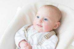 Happy smiling baby boy in a white chair Royalty Free Stock Photography