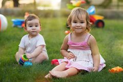 Happy Smiling Baby Brother and Toddler Sister Playing with Toys Stock Photography