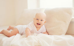 Happy smiling baby crawls home in white room near window Stock Photos