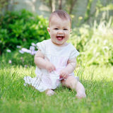 A happy smiling baby in a dress sitting on a grass Stock Images