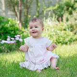 A happy smiling baby in a dress sitting on a grass Stock Photos