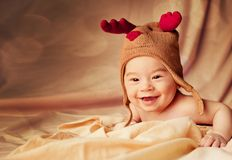 Happy smiling baby dressed in christmas deer hat stock photography