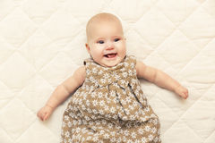 Happy smiling baby girl on blanket in bed Royalty Free Stock Images