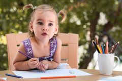 Happy Smiling Baby Girl Drawing Pictures Outdoors. In Garden in Summer Time royalty free stock images