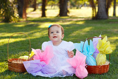Happy smiling baby girl with Easter chocolate eggs on green gras Stock Photo