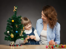 Happy smiling baby girl and her mummy decorate the Christmas tree Royalty Free Stock Images