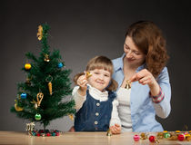 Happy smiling baby girl and her mummy decorates the Christmas tr Royalty Free Stock Photos
