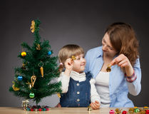 Happy smiling baby girl and her mummy decorates the Christmas tr Royalty Free Stock Photo