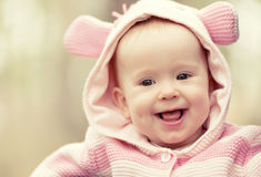 Happy smiling baby girl in pink hood with ears Stock Photo