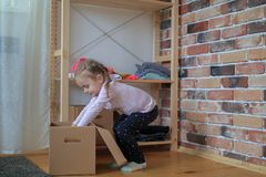 Happy baby girl is putting clothes in cardboard box royalty free stock image