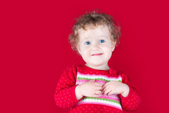 Happy smiling baby girl in a red Christmas jacket Royalty Free Stock Photography