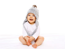 Happy smiling baby in grey knitted hat on white background. Happy smiling baby in grey knitted hat on a white background Stock Photos