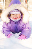 Happy smiling baby lying in the snow. In snowdrift. Merry winter. Child wearing a purple jumpsuit and a warm fluffy hat Royalty Free Stock Photos