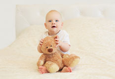 Happy smiling baby playing with teddy bear on bed home Stock Image