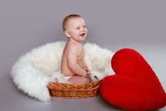 Happy smiling baby with red heart sitting in basket Stock Photo