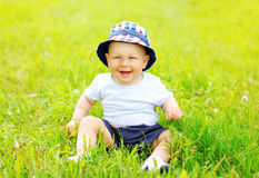 Happy smiling baby sitting on grass in sunny summer Stock Image