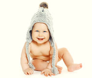 Happy smiling baby sitting in grey knitted hat Stock Photos