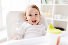 Happy smiling baby sitting in highchair at home. Childhood and people concept - happy smiling little baby sitting in highchair at home Royalty Free Stock Photos