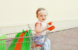 Happy smiling baby sitting in trolley cart with shopping bags Stock Photos