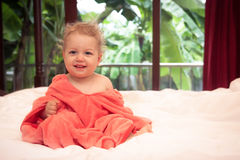 Happy smiling baby in soft pink blanket on white bed sheets in villa bedroom looking at camera with blurred tropical background an Stock Photo