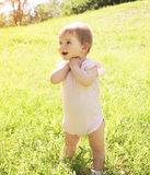 Happy smiling baby standing on grass in sunny summer Royalty Free Stock Images