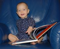 A happy smiling baby toddler sits in a big blue armchair flipping a page of a book. stock photography