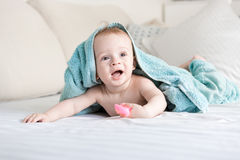 Happy smiling baby under blue towel crawling on bed with white s stock images