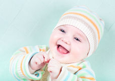 Happy smiling baby in a warm striped knitted sweat Stock Photos