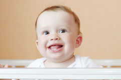 Happy smiling baby in white bed Royalty Free Stock Photos