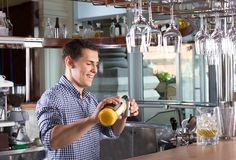 Happy smiling bartender pouring drink into a steel jigger. Stock Photos