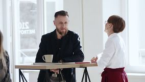 Happy smiling bearded middle aged male boss talking to young colleague woman standing at trendy loft office table. Happy smiling bearded middle aged male boss stock footage