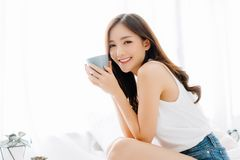 Free Happy Smiling Beautiful Asian Woman Awaking With Cup Of Coffee And Looking At Camera In The Bedroom. Lazy Day Off Concept Stock Photos - 153319413