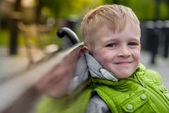 Happy smiling beautiful blonde boy relaxing on a bench Stock Images