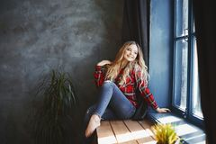 Happy and smiling beautiful blonde girl in jeans and red plaid shirt, sits and posing near the window and looks outside royalty free stock photos