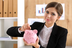 Happy smiling beautiful businesswoman putting pin money into pin Royalty Free Stock Photo