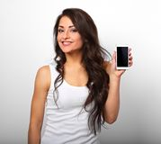 Happy smiling beautiful excited woman holding and advertising mo. Bile phone on white background with empty copy space stock photos