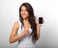 Happy smiling beautiful excited woman holding and advertising mo. Bile phone and showing thumb up sign on white background with empty copy space Stock Images