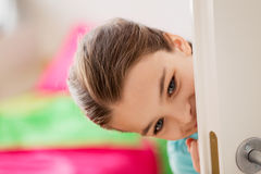 Happy smiling beautiful girl behind door at home Stock Photos