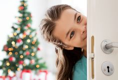 Happy smiling beautiful girl behind door at home Stock Photography