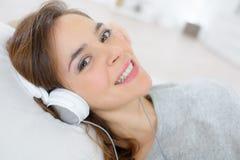 Happy smiling beautiful girl listening to music through headphones stock photos