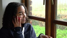 Happy smiling beautiful mixed race African American girl teenagersitting by a window talking on her mobile cell phone. Happy smiling beautiful mixed race African stock video footage