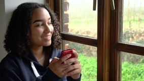 African American girl teenager young woman sitting by a window using her mobile cell phone or smartphone for social media or texti stock footage