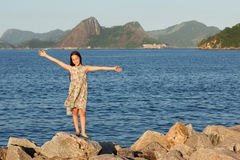 Happy smiling beautiful teen girl standing on stones with long b Stock Images