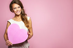 Happy smiling beautiful woman holding pink heart. Female model holding Valentine Day and Love symbol. Pink background Royalty Free Stock Image