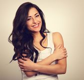 Happy smiling beautiful woman hugging herself with natural emoti. Onal enjoying face on white background. Love concept. Toned closeup portrait Royalty Free Stock Images