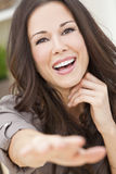 Happy Smiling Beautiful Woman Reaching to Camera. Portrait of a beautiful brunette young woman with perfect teeth smiling laughing and reaching to camera royalty free stock photography