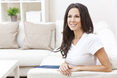 Happy Smiling Beautiful Woman Sitting on Sofa Stock Photos