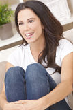 Happy Smiling Beautiful Woman Sitting on Sofa. Portrait of a beautiful brunette young woman in jeans and t-shirt smiling siting on her sofa at home royalty free stock photo