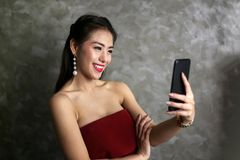 Happy smiling beautiful young woman in red party dress shoo. Ting selfie on front camera of smart cell phone stock photo