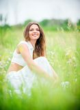 Happy smiling beautiful young woman sitting among grass and flowers Stock Photography